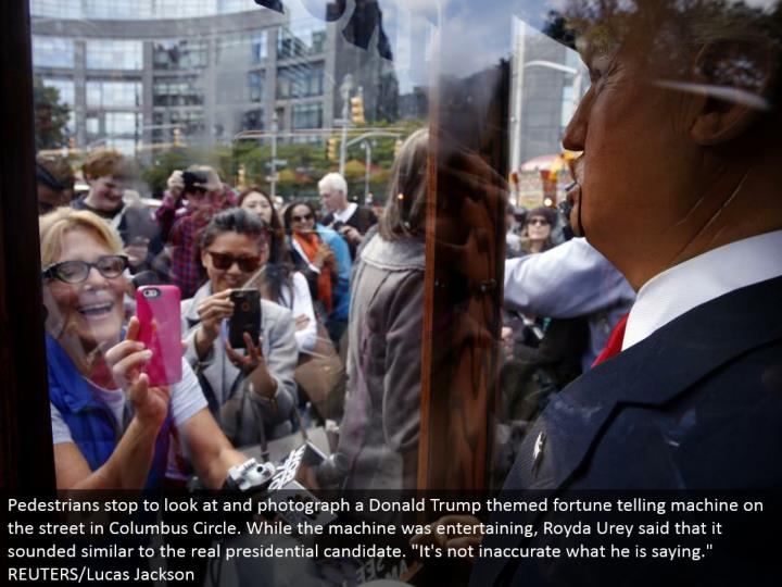 """Pedestrians stop to take a gander at and photo a Donald Trump themed fortune telling machine in the city in Columbus Circle. While the machine was engaging, Royda Urey said that it sounded like the genuine presidential applicant. """"It's not wrong what he is stating.""""  REUTERS/Lucas Jackson"""