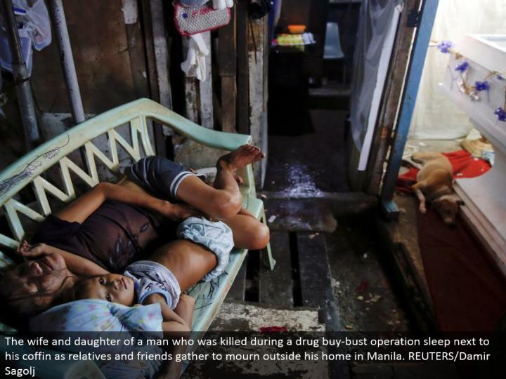 The spouse and little girl of a man who was slaughtered amid a medication purchase bust operation rest alongside his box as relatives and companions accumulate to grieve outside his home in Manila. REUTERS/Damir Sagolj