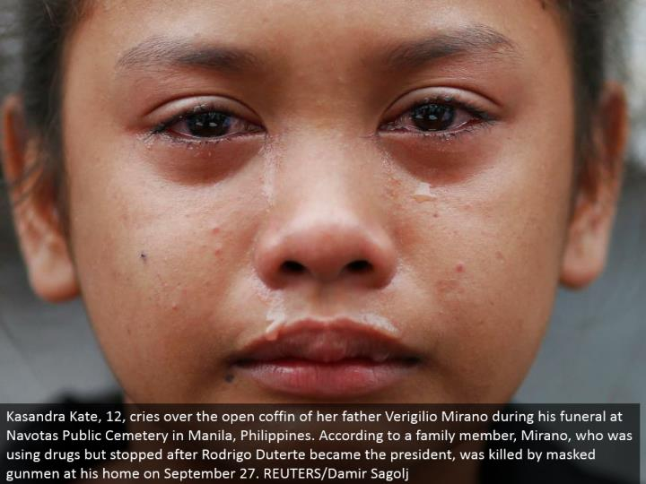 Kasandra Kate, 12, cries over the open casket of her dad Verigilio Mirano amid his burial service at...