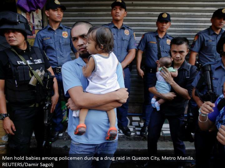 Men hold babies among policemen amid a medication attack in Quezon City, Metro Manila. REUTERS/Damir Sagolj