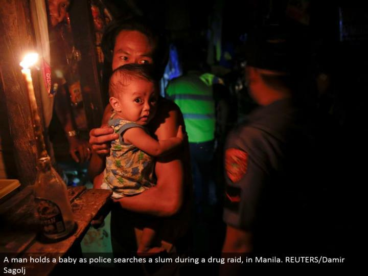 A man holds an infant as police inquiries a ghetto amid a medication strike, in Manila. REUTERS/Damir Sagolj