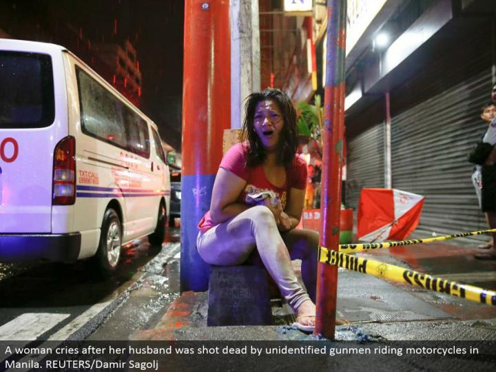 A lady cries after her significant other was shot dead by unidentified shooters riding cruisers in M...