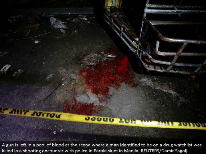 A firearm is left in a pool of blood at the scene where a man recognized to be on a medication watchlist was executed in a shooting experience with police in Parola ghetto in Manila. REUTERS/Damir Sagolj