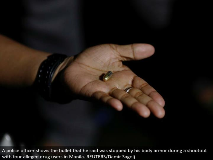 A cop demonstrates the projectile that he said was halted by his body reinforcement amid a shootout with four affirmed tranquilize clients in Manila. REUTERS/Damir Sagolj