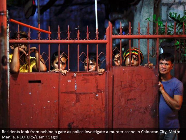 Residents look from behind an entryway as police examine a murder scene in Caloocan City, Metro Manila. REUTERS/Damir Sagolj
