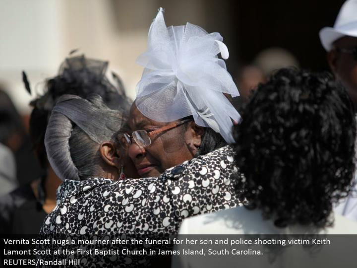 Vernita Scott embraces a griever after the memorial service for her child and police shooting casualty Keith Lamont Scott at the First Baptist Church in James Island, South Carolina.  REUTERS/Randall Hill
