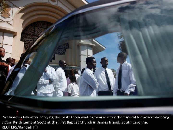 Pall bearers talk subsequent to conveying the coffin to a sitting tight funeral wagon after the memorial service for police shooting casualty Keith Lamont Scott at the First Baptist Church in James Island, South Carolina. REUTERS/Randall Hill