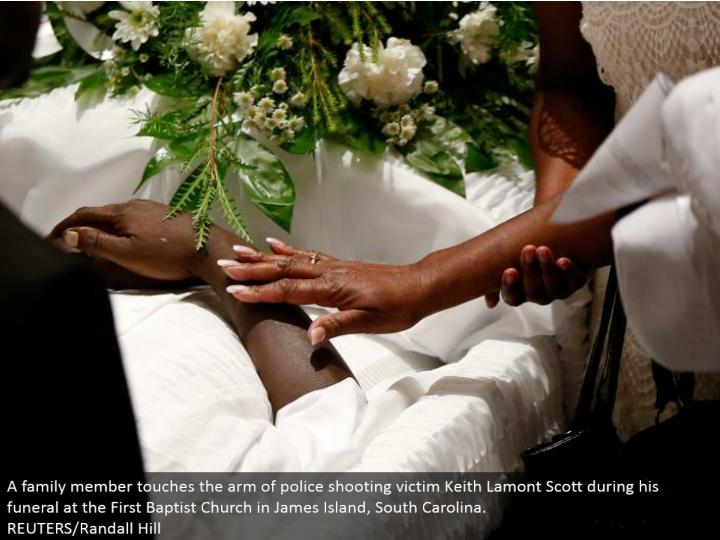 A relative touches the arm of police shooting casualty Keith Lamont Scott amid his memorial service ...