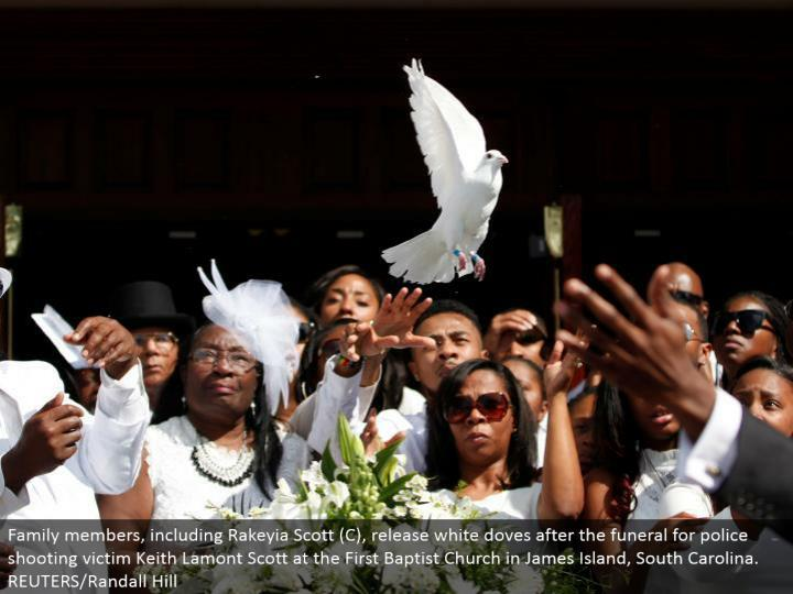 Family individuals, including Rakeyia Scott (C), discharge white birds after the burial service for ...