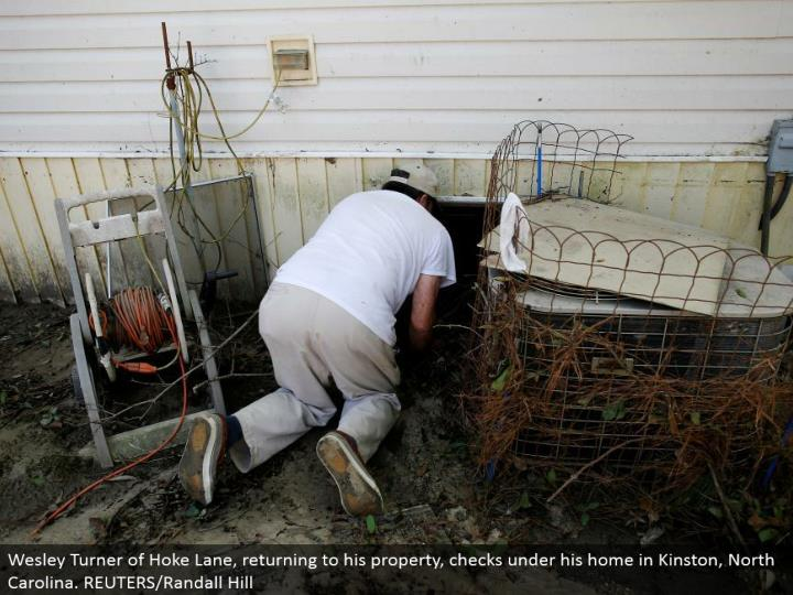 Wesley Turner of Hoke Lane, coming back to his property, checks under his home in Kinston, North Carolina. REUTERS/Randall Hill