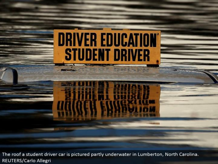 The rooftop an understudy driver auto is envisioned halfway submerged in Lumberton, North Carolina. REUTERS/Carlo Allegri