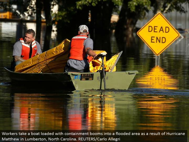 Workers bring a pontoon stacked with regulation blasts into an overwhelmed region as a consequence of Hurricane Matthew in Lumberton, North Carolina. REUTERS/Carlo Allegri