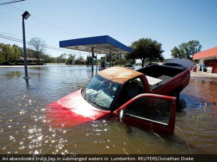 An relinquished truck lies in submerged waters in Lumberton. REUTERS/Jonathan Drake