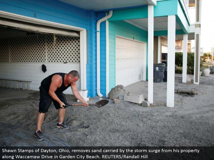 Shawn Stamps of Dayton, Ohio, evacuates sand conveyed by the tempest surge from his property along Waccamaw Drive in Garden City Beach. REUTERS/Randall Hill