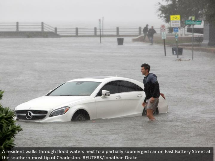 A inhabitant strolls through surge waters alongside a somewhat submerged auto on East Battery Street at the southern-most tip of Charleston. REUTERS/Jonathan Drake