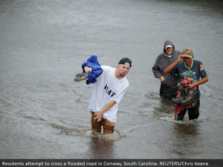 Residents endeavor to cross an overflowed street in Conway, South Carolina. REUTERS/Chris Keane