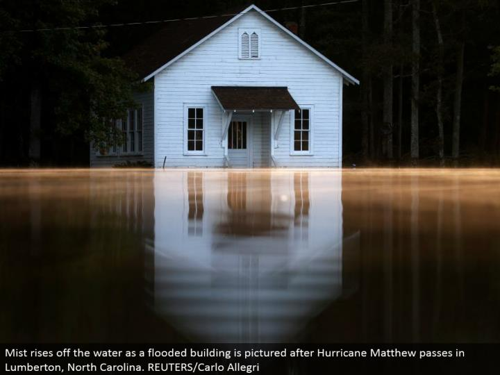 Mist ascends off the water as an overwhelmed building is envisioned after Hurricane Matthew goes in Lumberton, North Carolina. REUTERS/Carlo Allegri