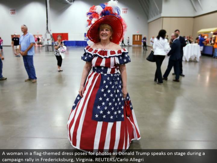 A lady in a banner themed dress postures for photographs as Donald Trump talks in front of an audience amid a crusade rally in Fredericksburg, Virginia. REUTERS/Carlo Allegri