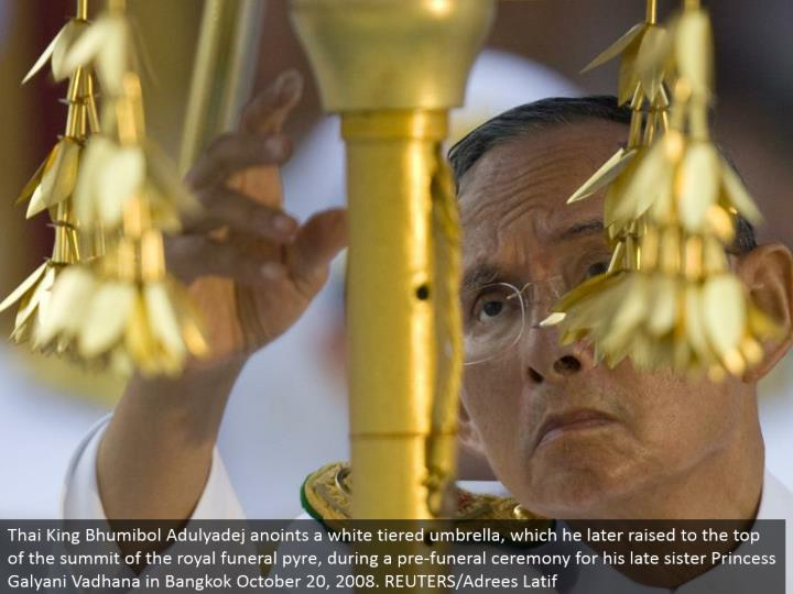 Thai King Bhumibol Adulyadej blesses a white layered umbrella, which he later raised to the highest point of the summit of the regal memorial service fire, amid a pre-burial service function for his late sister Princess Galyani Vadhana in Bangkok October 20, 2008. REUTERS/Adrees Latif