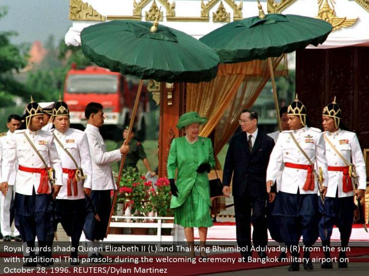 Royal watches shade Queen Elizabeth II (L) and Thai King Bhumibol Adulyadej (R) from the sun with conventional Thai parasols amid the inviting function at Bangkok military airplane terminal on October 28, 1996. REUTERS/Dylan Martinez