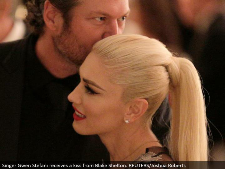 Singer Gwen Stefani gets a kiss from Blake Shelton. REUTERS/Joshua Roberts