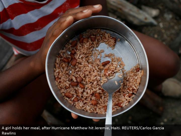 A young lady holds her supper, after Hurricane Matthew hit Jeremie, Haiti. REUTERS/Carlos Garcia Rawlins