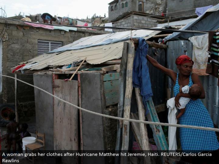 A lady gets her garments after Hurricane Matthew hit Jeremie, Haiti. REUTERS/Carlos Garcia Rawlins