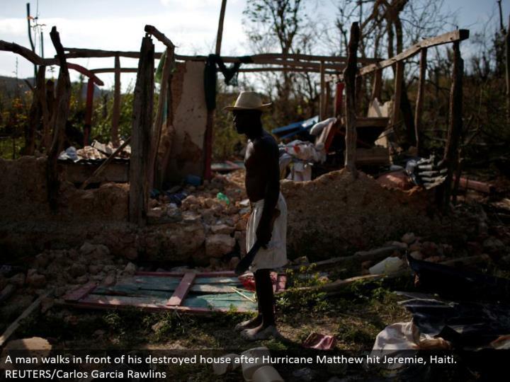 A man strolls before his wrecked house after Hurricane Matthew hit Jeremie, Haiti. REUTERS/Carlos Garcia Rawlins