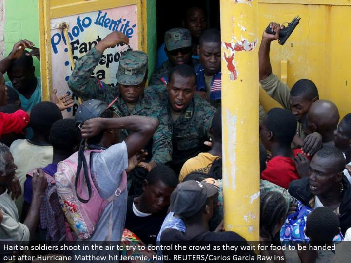 Haitian officers shoot noticeable all around to attempt to control the group as they sit tight for nourishment to be passed out after Hurricane Matthew hit Jeremie, Haiti. REUTERS/Carlos Garcia Rawlins