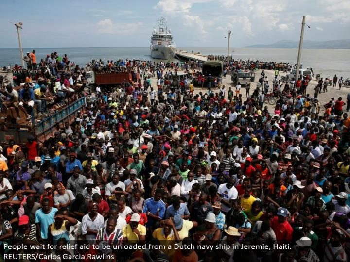 People sit tight for alleviation help to be emptied from a Dutch naval force transport in Jeremie, H...