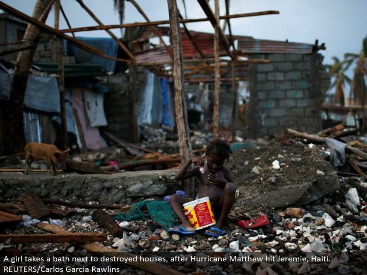 A young lady washes up by decimated houses, after Hurricane Matthew hit Jeremie, Haiti. REUTERS/Carlos Garcia Rawlins