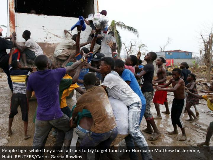 People battle while they pounce upon a truck to attempt to get sustenance after Hurricane Matthew hit Jeremie, Haiti. REUTERS/Carlos Garcia Rawlins