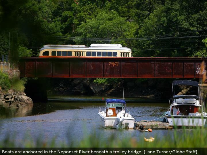 Boats are tied down in the Neponset River underneath a trolley connect. (Path Turner/Globe Staff)