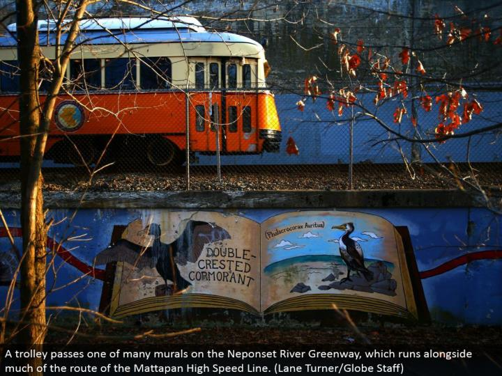 A trolley passes one of numerous wall paintings on the Neponset River Greenway, which keeps running ...