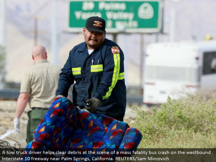 A tow truck driver clears flotsam and jetsam at the scene of a mass casualty transport crash on the westward Interstate 10 road close Palm Springs, California. REUTERS/Sam Mircovich