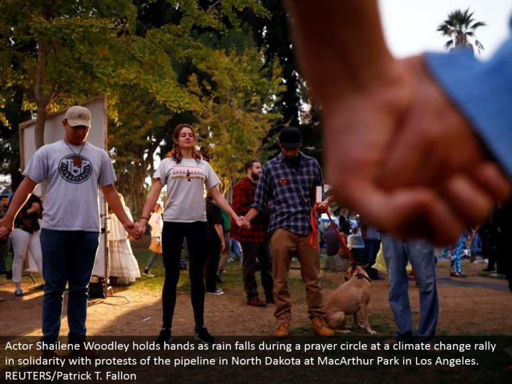 Actor Shailene Woodley clasps hands as rain falls amid a supplication hover at an environmental change rally in solidarity with challenges of the pipeline in North Dakota at MacArthur Park in Los Angeles.  REUTERS/Patrick T. Fallon