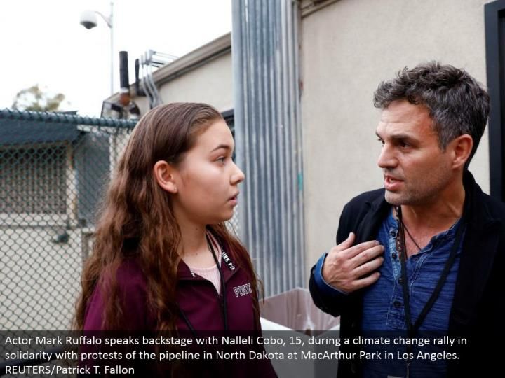 Actor Mark Ruffalo talks backstage with Nalleli Cobo, 15, amid an environmental change rally in solidarity with challenges of the pipeline in North Dakota at MacArthur Park in Los Angeles. REUTERS/Patrick T. Fallon