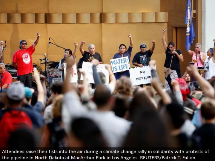 Attendees raise their clench hands into the air amid an environmental change rally in solidarity with dissents of the pipeline in North Dakota at MacArthur Park in Los Angeles. REUTERS/Patrick T. Fallon