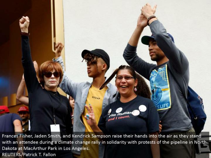 Frances Fisher, Jaden Smith, and Kendrick Sampson raise their hands into the air as they remain with a participant amid an environmental change rally in solidarity with challenges of the pipeline in North Dakota at MacArthur Park in Los Angeles.  REUTERS/Patrick T. Fallon
