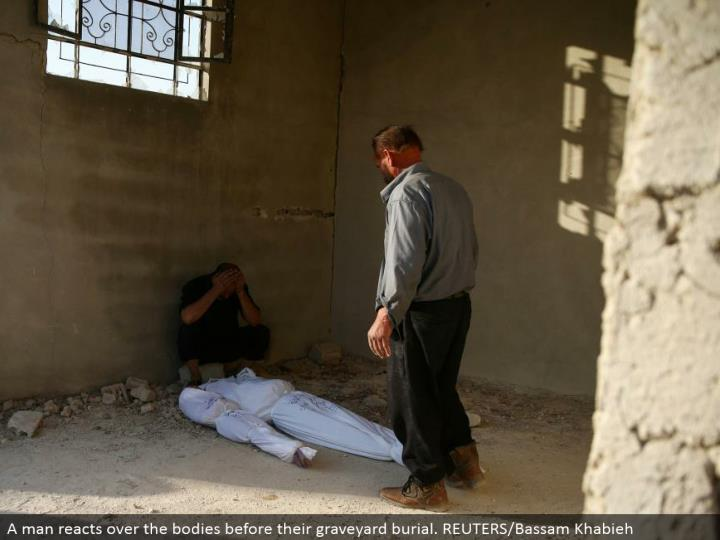 A man responds over the bodies before their memorial park internment. REUTERS/Bassam Khabieh