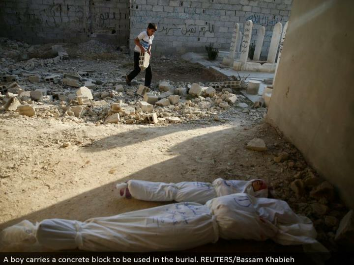 A kid conveys a solid square to be utilized as a part of the entombment. REUTERS/Bassam Khabieh