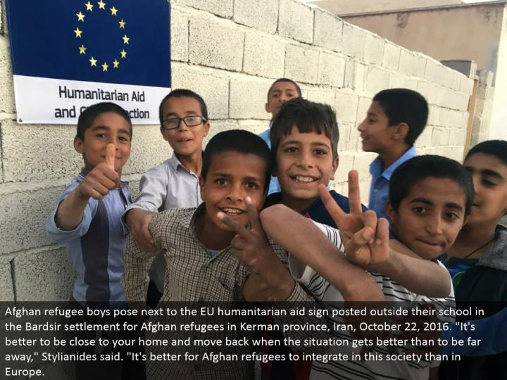 "Afghan displaced person young men posture alongside the EU philanthropic guide sign posted outside their school in the Bardsir settlement for Afghan outcasts in Kerman region, Iran, October 22, 2016. ""It's ideal to be near your home and move back when the circumstance improves than to be far away,"" Stylianides said. ""It's better for Afghan displaced people to coordinate in this general public than in Europe."