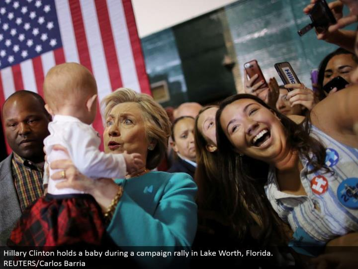 Hillary Clinton holds a child amid a crusade rally in Lake Worth, Florida.  REUTERS/Carlos Barria