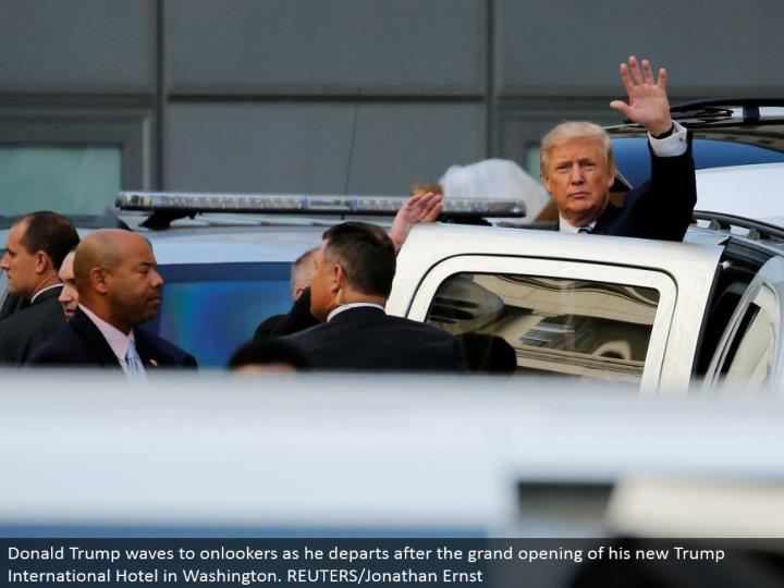 Donald Trump waves to spectators as he withdraws after the great opening of his new Trump International Hotel in Washington. REUTERS/Jonathan Ernst