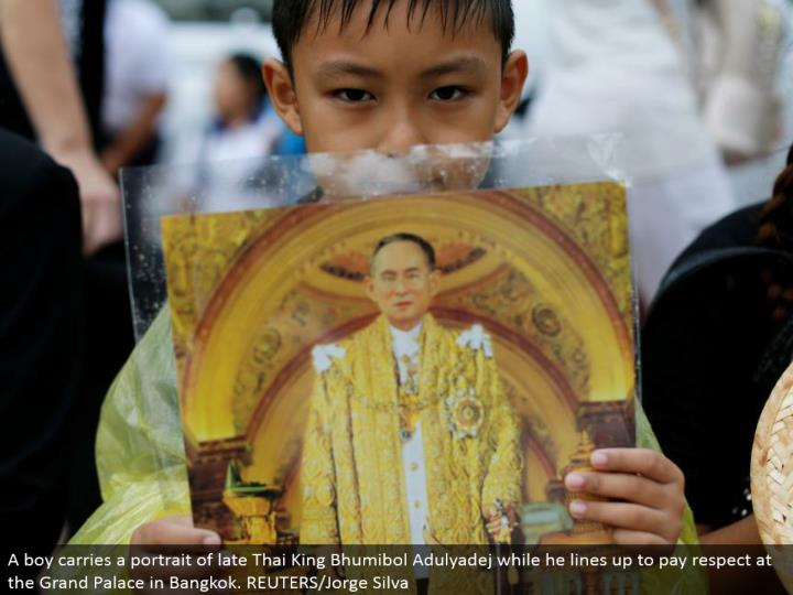 A kid conveys a representation generally Thai King Bhumibol Adulyadej while he lines up to pay regard at the Grand Palace in Bangkok. REUTERS/Jorge Silva