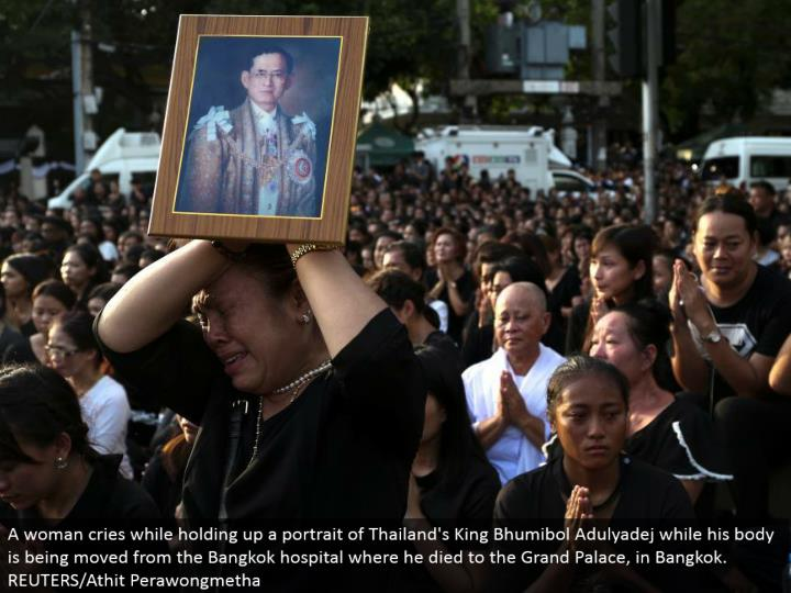 A lady cries while holding up a picture of Thailand's King Bhumibol Adulyadej while his body is being moved from the Bangkok healing center where he passed on to the Grand Palace, in Bangkok. REUTERS/Athit Perawongmetha