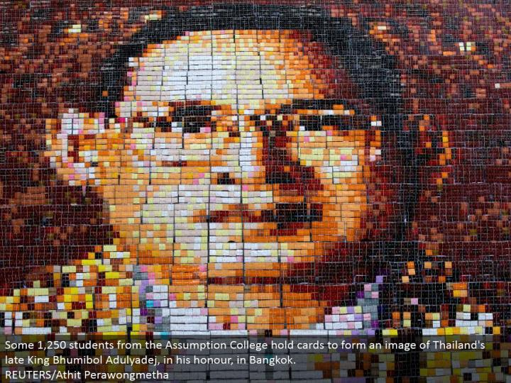 Some 1,250 understudies from the Assumption College hold cards to shape a picture of Thailand's late...