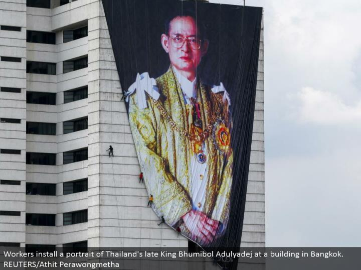 Workers introduce a picture of Thailand's late King Bhumibol Adulyadej at a working in Bangkok.  REUTERS/Athit Perawongmetha