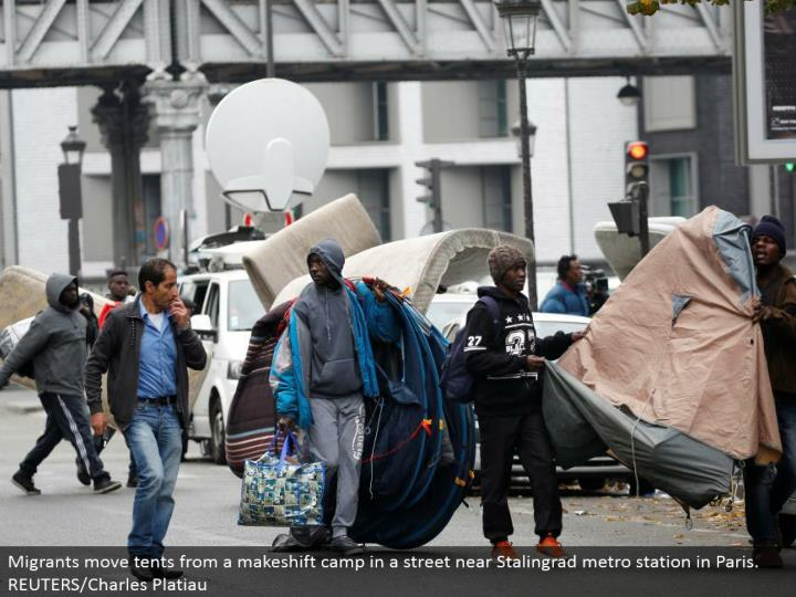 Migrants move tents from an alternative camp in a road close Stalingrad metro station in Paris.  REUTERS/Charles Platiau