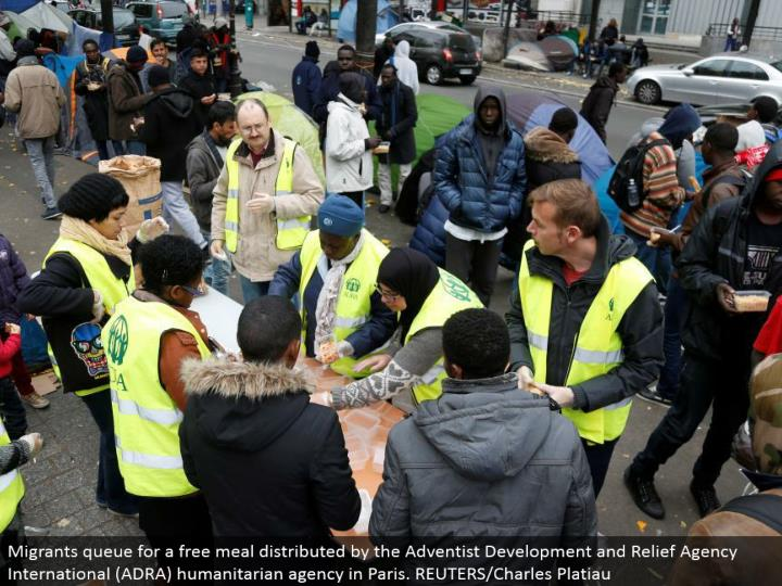Migrants line for a free feast appropriated by the Adventist Development and Relief Agency International (ADRA) helpful office in Paris. REUTERS/Charles Platiau